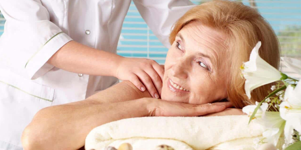An Elder Woman Relaxing While Massage Therapy By A Experienced Massage Therapist.