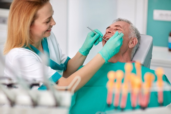 Dentist examining senior patient mouth with angled mirror and scaler during treatment