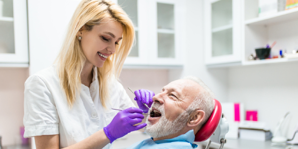 An Image Representing A Leading Dentist Giving Dental Treatmet To A Senior Citizen.