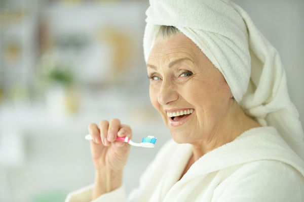 An Image of an elder woman brushing her teeth in the bathroom representing the healthy teeth concept.